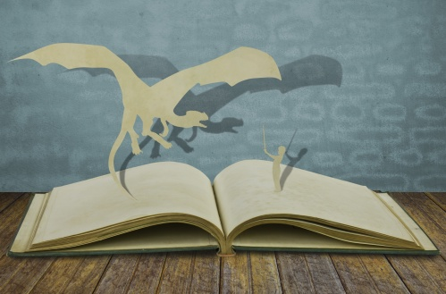 Paper cut of dragon and child hold sword on old book