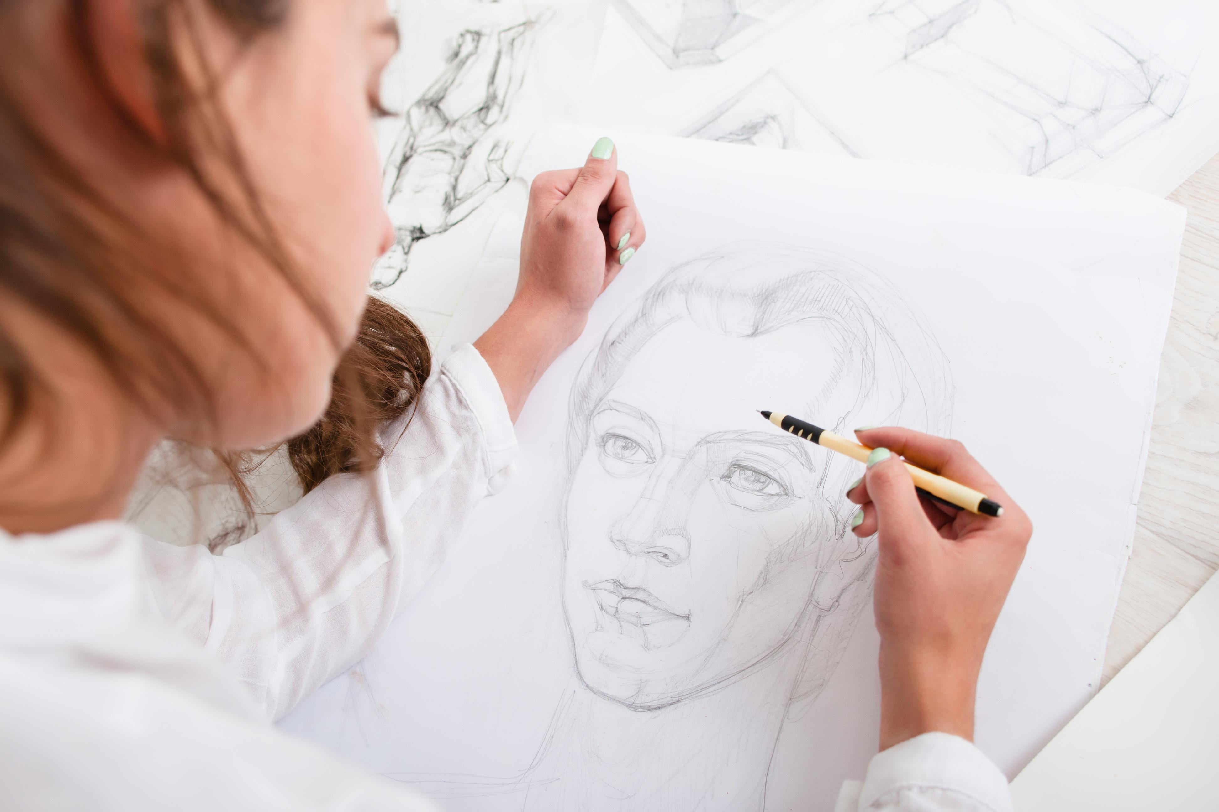 Artist drawing pencil portrait close-up